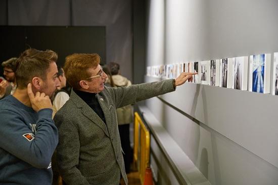 Visitantes mirando fotos en la exposición