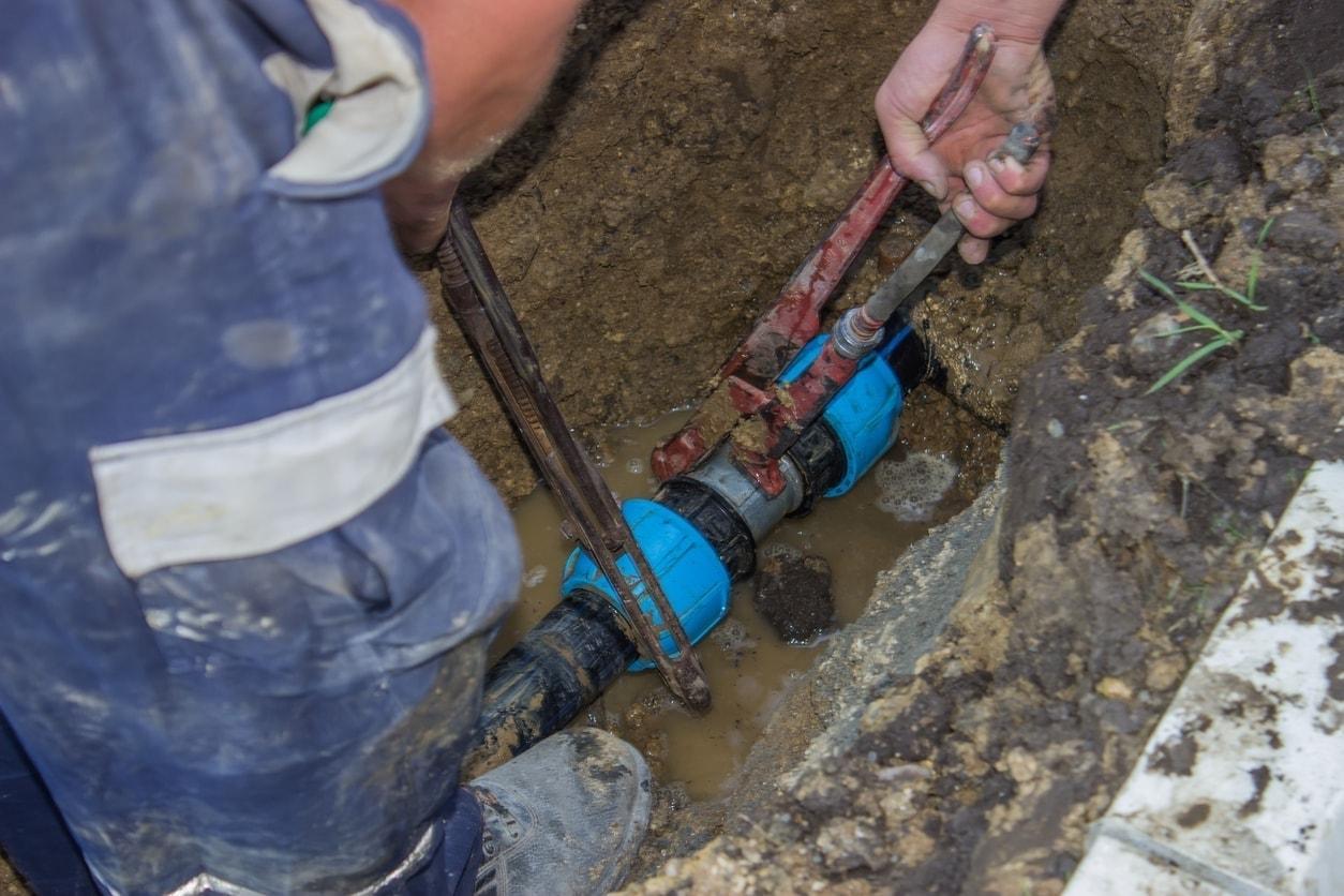 Trabajadores arreglan una conexión de tuberías