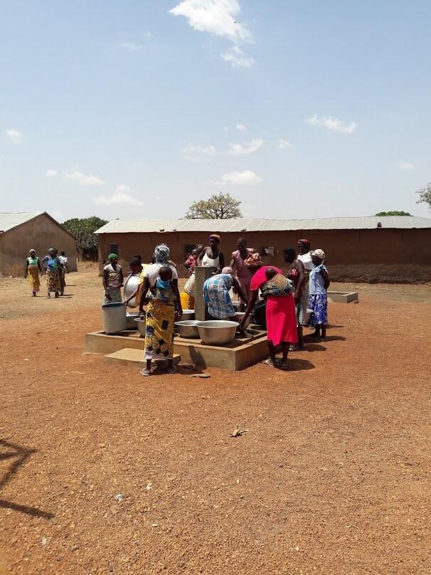 Mujeres y niñas cogiendo agua en las instalaciones