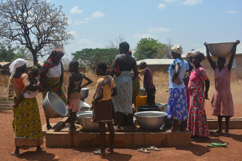 Imagen de mujeres y niñas cogiendo agua en una de las instalaciones de grifo