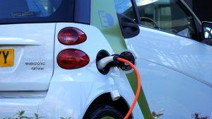 Parte trasera de un coche eléctrico de color blanco mientras se carga su batería