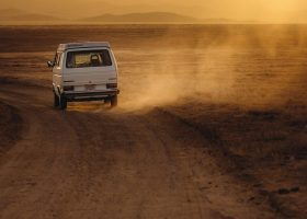 White color van crossing a lonely and desert road