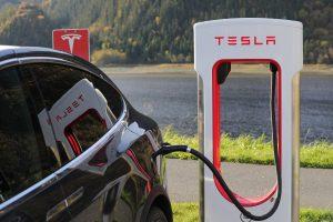 Tesla black car charging at a Tesla power station