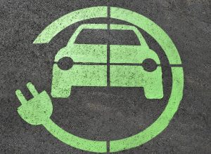 Green color symbol of an electric car painted on the asphalt in a charging spot