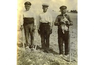 Tres Camineros de Villamanrique, Ciudad Real, sobre un terreno con palas y uno de ellos sosteniendo un perro, en 1930.