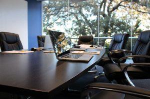 sala de reuniones con una amplia mesa y un portátil sobre ella