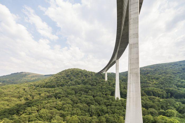 Imagen de carretera construida sobre paisaje verde, ejemplo de desarrollo sostenible