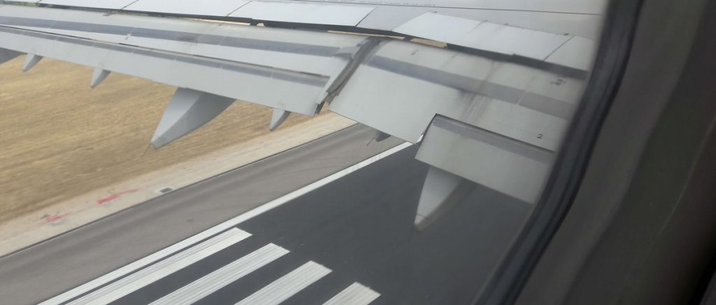 Image of the wing of an airplane and the track seen from the window