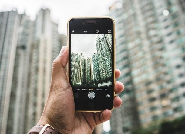 Someone holds a mobile phone in selfie mode, you see the landscape of a city