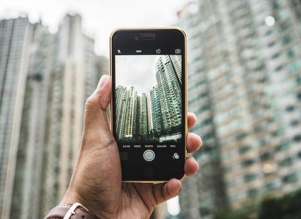 Alguien sujeta un móvil en modo selfie, se ve el paisaje de una ciudad borrosa