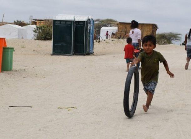A boy runs behind a tire on a dirt esplanade