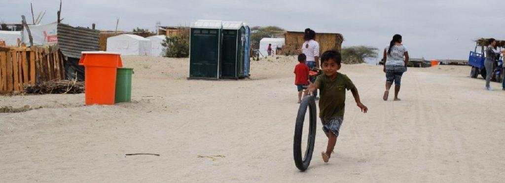 Un niño corre detrás de un neumático por una explanada de tierra
