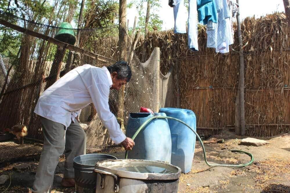 Imagn de un hombre usando la manguera que suministra agua corriente