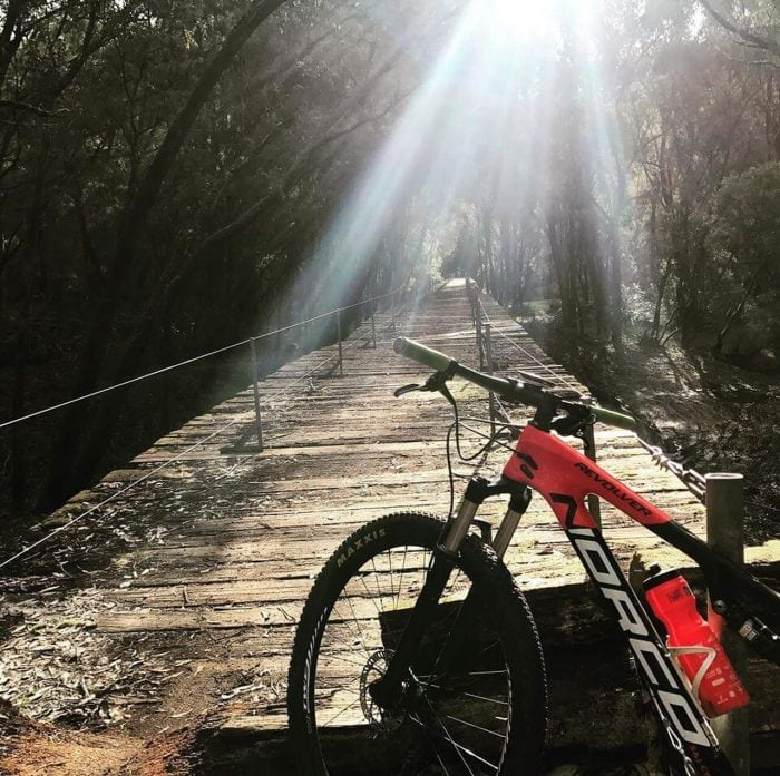 Photo of a wooden walkway and a bike