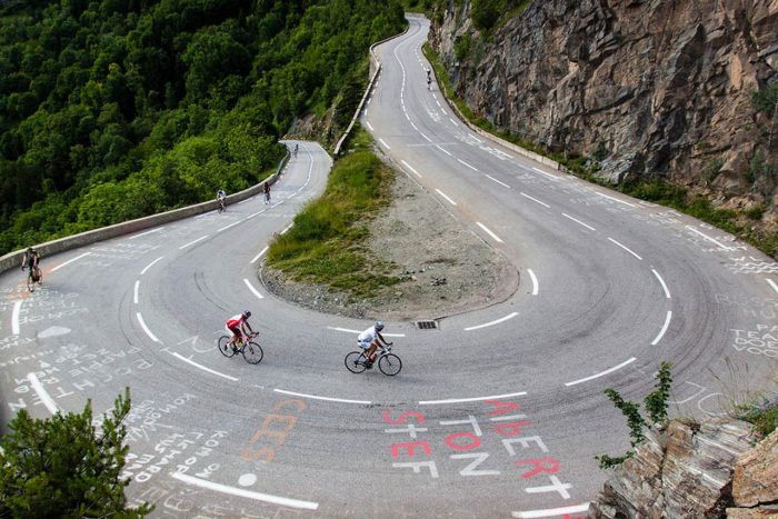Image of a curve in mountain road and 2 cyclists going up