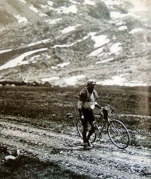 Imagen antigua de un ciclista sujetando la bicicleta
