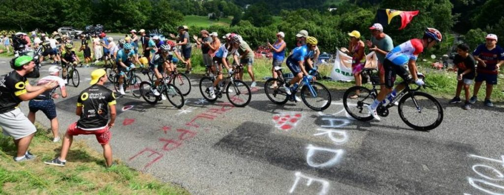 Imagen del Tour de Francia donde se ven ciclistas animados por aficionados y de fondo montañas verdes