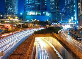 Imagen nocturna de una ciudad con rascacielos, carreteras y un tunel