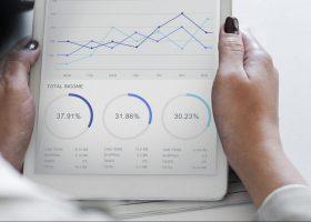 Foto de las manos de una majer sujetando una tablet con datos de la empresa
