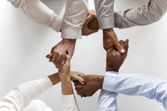 Photo of 4 people with their hands entwined