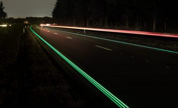 Imagen de una carretera de noche con las señales reflectantes
