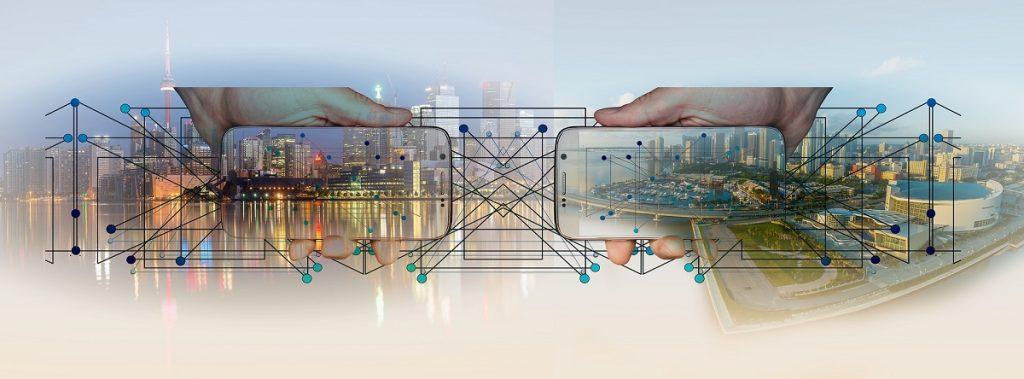 Dos smartphones encontrados simulan intercambiar gran volumen de datos. Una ciudad de fondo y dos manos que los sostienen