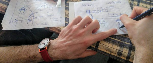 Foto de las manos de una persona que está dibujando esquemas en unas hojas
