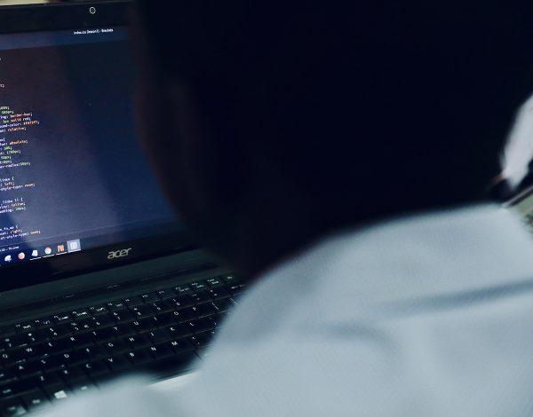 foto del hombro de una persona y un ordenadorportátil