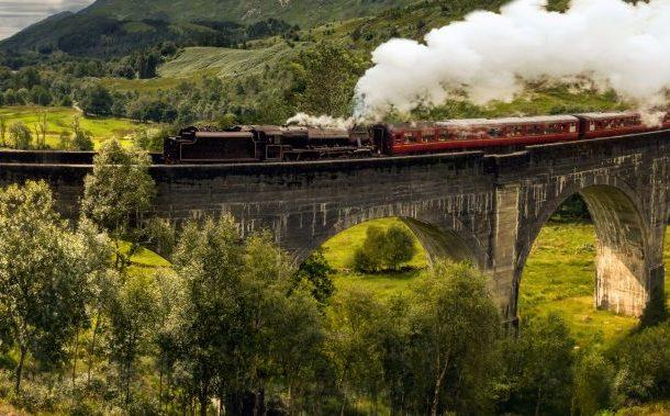 Foro de un puente de piedra por el que está pasando un tren