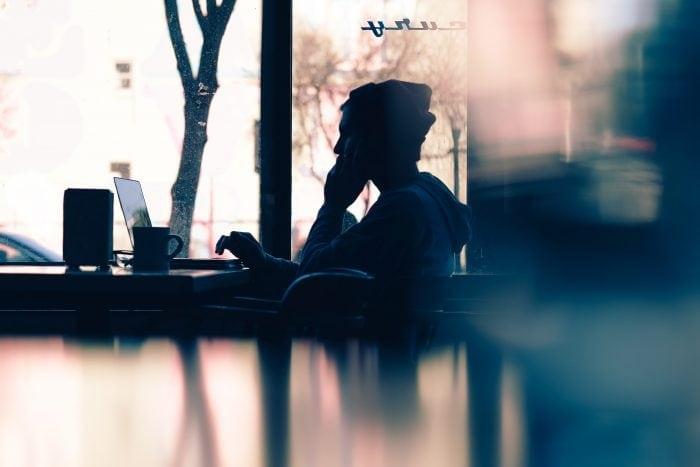 Foto de un chico sentado en la mesa de una cafeteria con un portatil