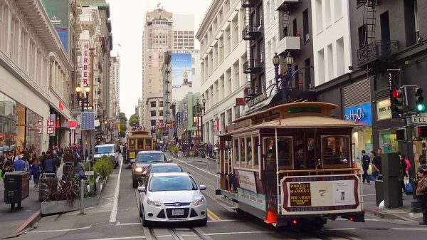 Image of a street in San Francisco where both cars and a tram circulate