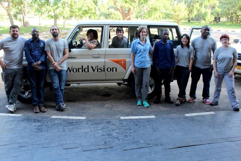 Imagen de un grupo de cooperantes de distintas organizaciones posando delante de un jeep