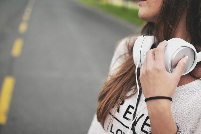 A girl holding headphones around her neck.