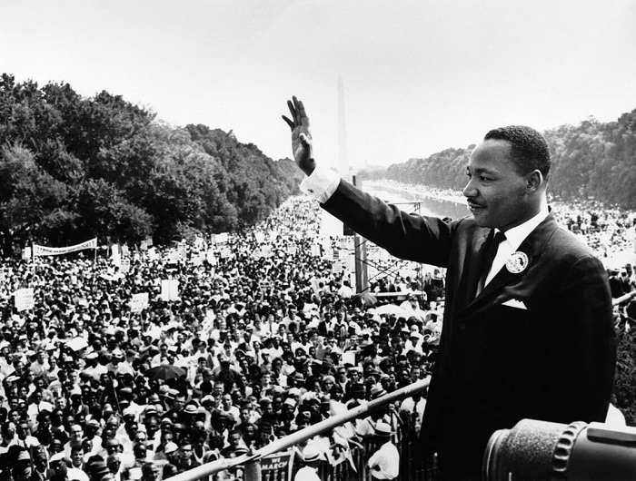 Martin Luther King, Jr. waves to protesters from the Lincoln Memorial