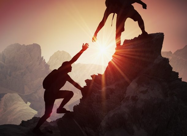 Silhouettes of two people climbing on mountain and helping.