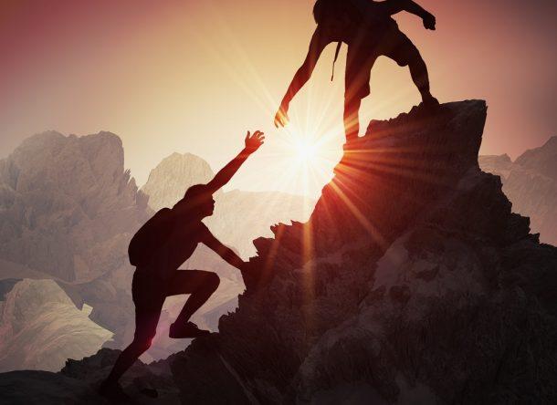 Siluetas de dos personas dándose la mano. Concepto de cooperación y trabajo en equipo