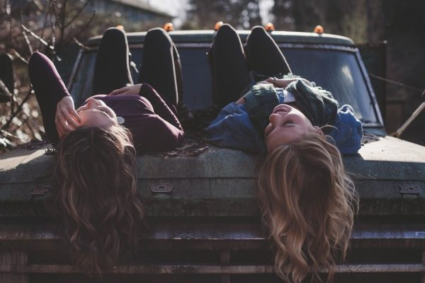 Two girls talking while lying on a car.