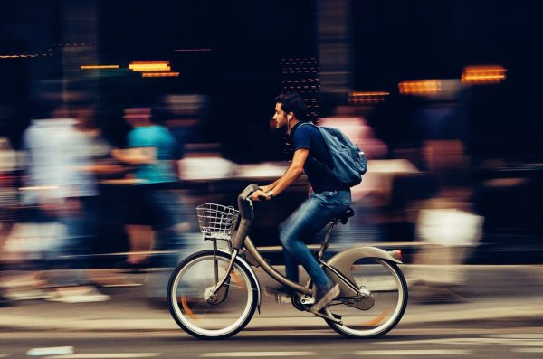 A man riding a bicycle getting to work.