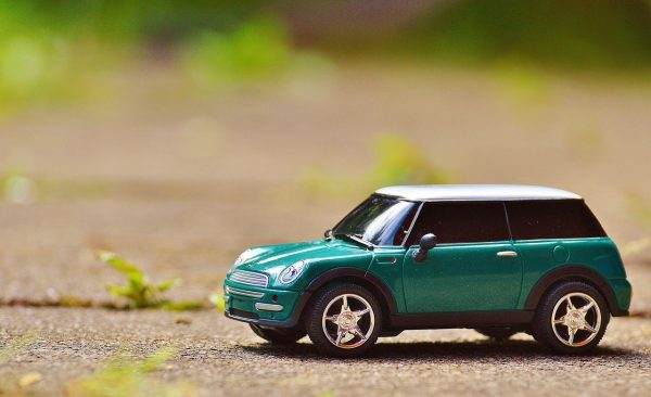A green scale model car on pavement.