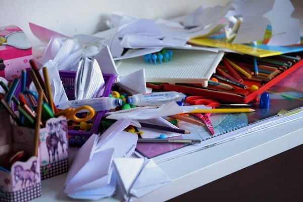 Una mesa de oficina desordenada con papeles, tijeras, lápices de colores, etc.