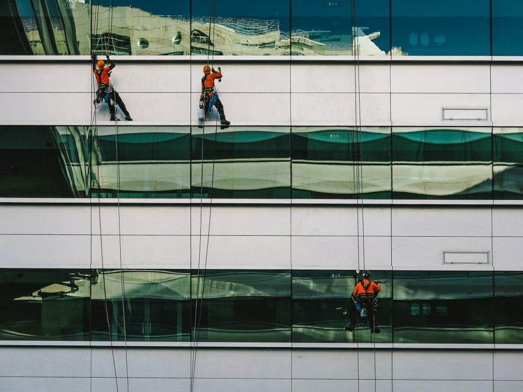 Trabajadores limpiando cristales en altura