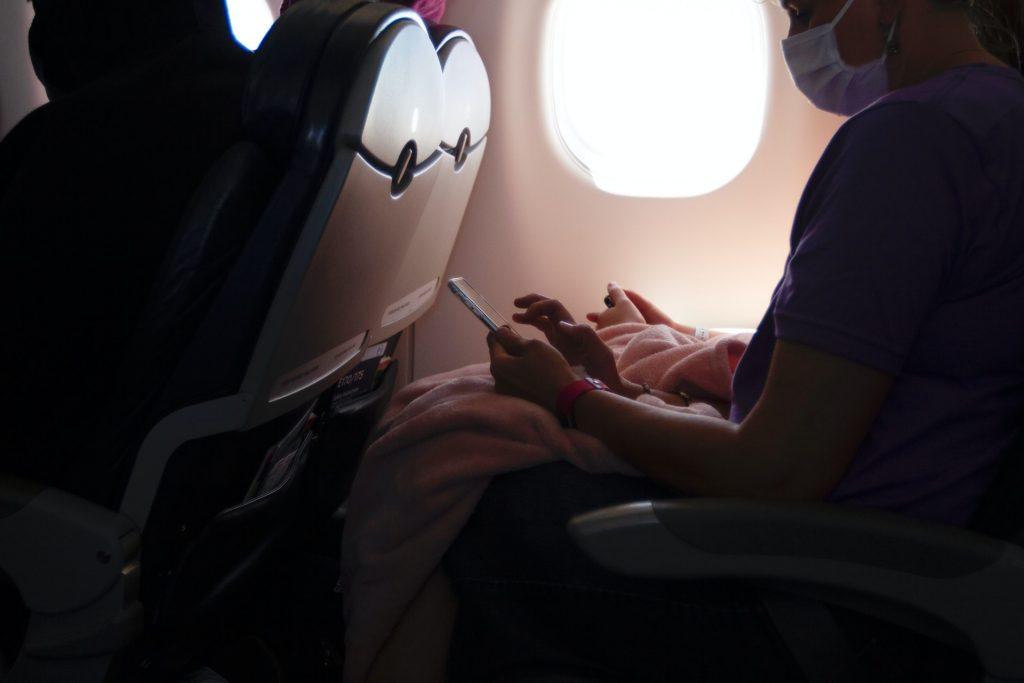 Persona usando la mascarilla dentro de un avión