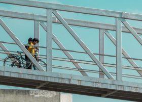 Niños cruzando la carretera por una pasarela