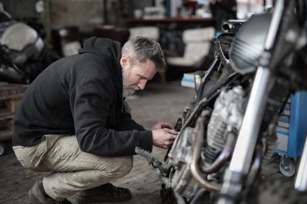 un hombre reparando una moto para prepararla para un viaje largo