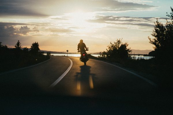 un hombre montando una moto al atardecer
