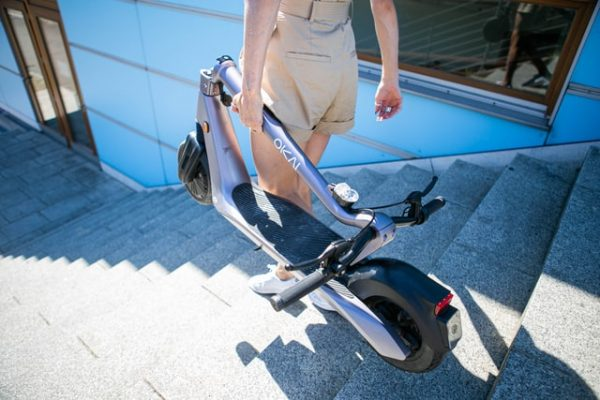 Mujer bajando un patinete eléctrico por las escaleras