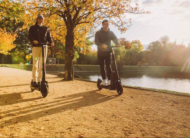 Hombre y mujer montados en patinetes eléctricos y pensando en lo ecológicos que son