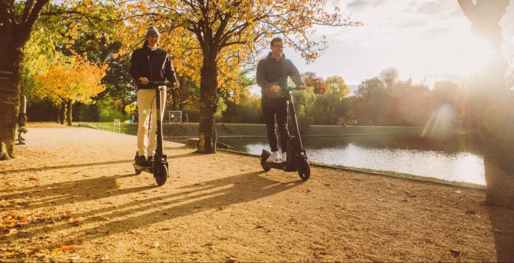 Man and woman riding and thinking about how eco-friendly are electric scooters.