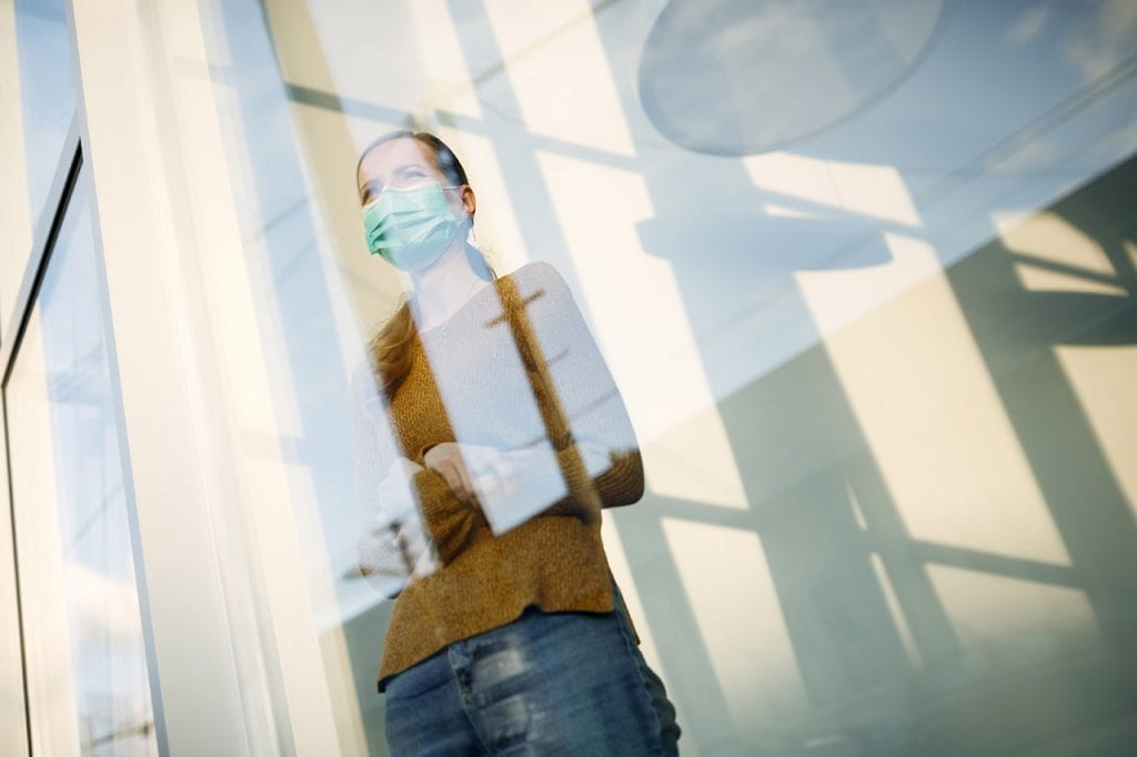 woman with face mask standing by the window