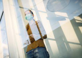 mujer con mascarilla junto a la ventana